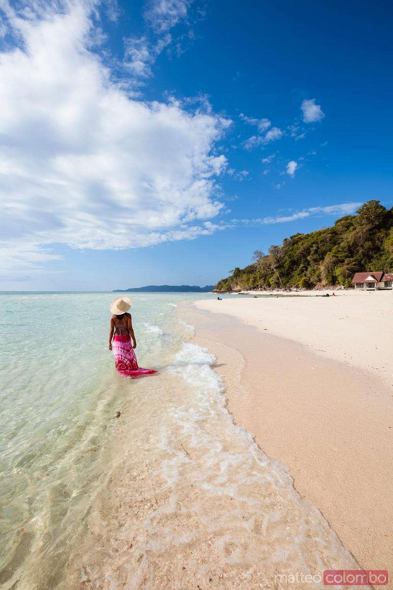 Woman with sarong on tropical beach, bamboo island, Thailand