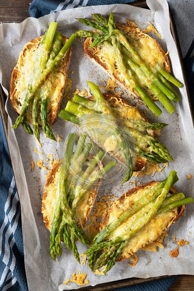 A tray of grilled cheese and asparagus on slices of sourdough bread.