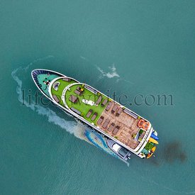 Aerial view of a Vietnamese luxury boat in Halong bay when oil spill in the sea. Ecological background. Environmental pollution.