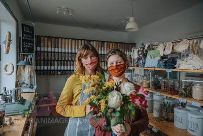 Female entrepreneur with clerk holding bunch of flowers while standing in retail store during pandemic