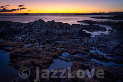 Tranquil sunset scene on rocky beach, on west coast of Scotland.