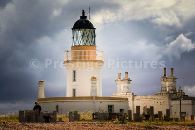 Beautiful sunlight on the Chanonry lighthouse contrasting against the dark broody sky behind
