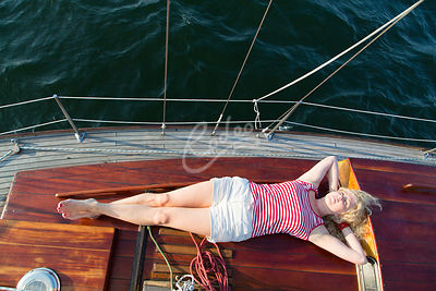 Nainen makaamassa purjeveneen kannella|||Woman relaxing on a deck of sailboat