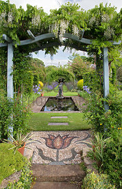 Wisteria on pergola over tulip mosaic designed by Maggie Howarth; rectangular pond featuring sculpture/fountain of a girl was...