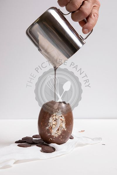 A hand pouring melted chocolate in to a Chocolate Easter egg