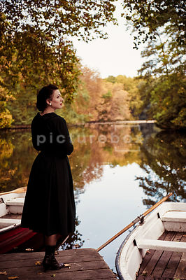 A vintage, mystery woman, looking out of over a lake.
