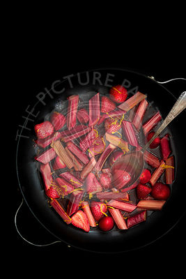 Roasted rhubarb and strawberries in syrup in a pan