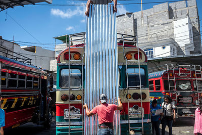 A man loads a sheet of corrugated iron into the top of a bus