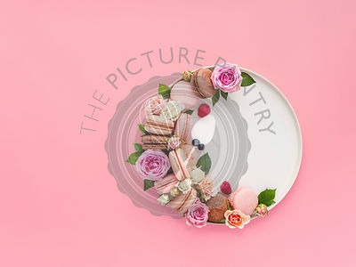 Creative layout with macarons, flowers and berries in white craft plate on pastel pink background