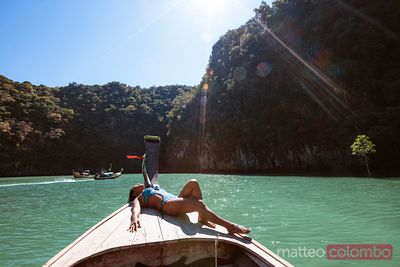 Asian woman in swimwear lying down on boat prow, Thailand