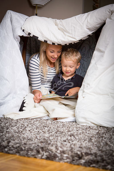 Äiti ja poika lukevat olohuoneeseen tehdyssä majassa|||Mother and a boy playing in the blanket hut at the livingroom
