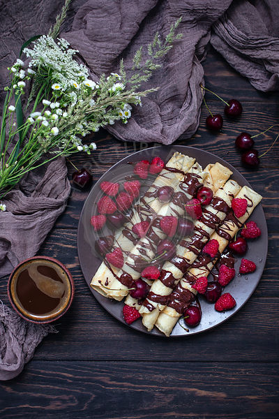 Crepes drizzled with chocolate and topped with fresh cherries and raspberries