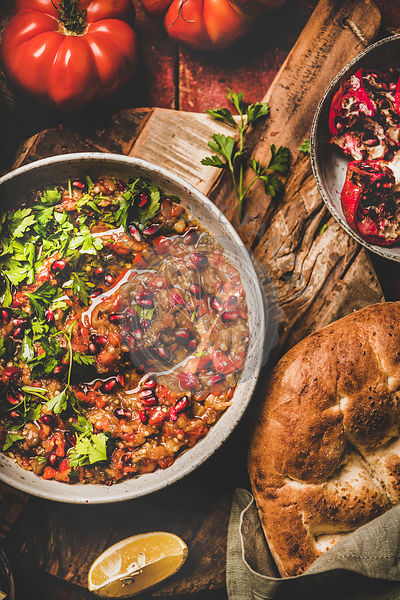 Babaganoush cold dip seasoned with parsley, pomegranate seeds and flatbread