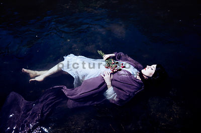 A clothed woman floating in a river.