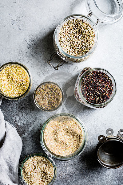 A collection of seeds and grains on a grey background, buckwheat, brown rice, quinoa, millet, amaranth, and flax seeds