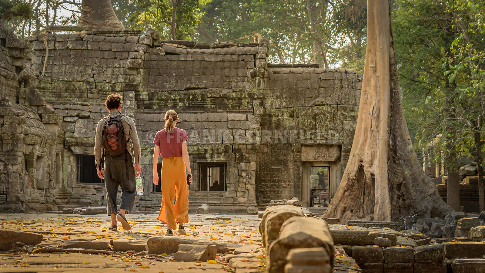 A unidentfied man and woman walking towards Ta Phrom temple within the Angkor Wat temple complex in Siem Reap, Cambodia.