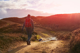 A hiker and their dog walking along a dirt track across Edmundbyers moor and sunset.