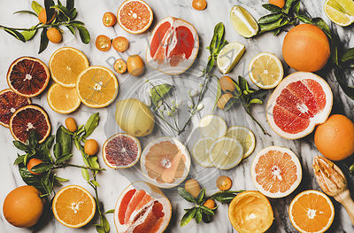Flat-lay of fresh oranges, lemons, kumquats, grapefruits and blossom flowers