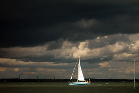 #061936,  Sailing boat urgently heading for port to avoid the gathering cumulus storm clouds at sea.
