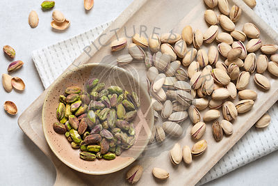 Roasted and salted pistachio nuts in shells with a bowl of kernals.